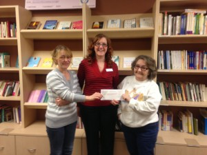 Samantha (L) and her mother Ronnie (R) present our development director Amber with a check from their event.